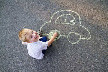 Boy drawing car with chalk