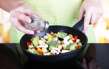 Hands cooking vegetable ragout in pan in kitchen
