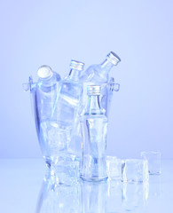 Minibar bottles in bucket with ice cubes, isolated on white