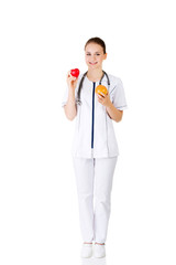 Female doctor holding healthy grapefruit and red heart.