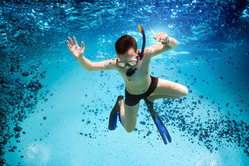 Wall Mural - Teenager in the mask and snorkel swim underwater.