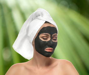 Woman receiving a mud mask on the green background