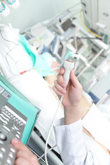 Doctor holding an ultrasound probe in the ICU.