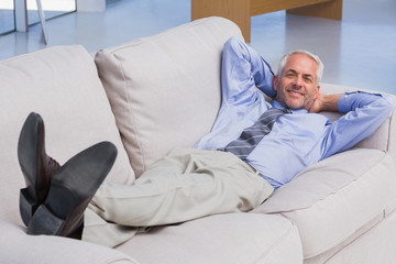 Businessman lying on sofa with his feet up smiling at camera