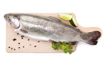Fresh trout on wooden kitchen board.