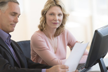 Businesswoman With Colleague Reading Document At Desk