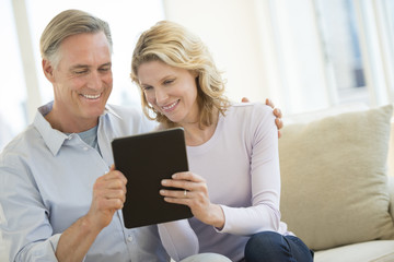 Couple Using Digital Tablet At Home