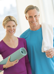 Couple With Water Bottle; Exercise Mat And Towel In Gym