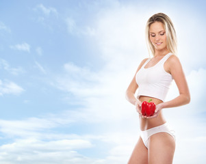 A young blond woman in white lingerie holding a paprika