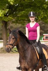 Mädchen sitzt auf ihrem Pony