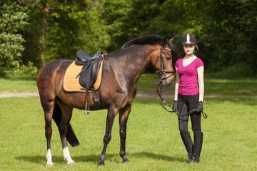 Mädchen steht neben ihrem Pferd