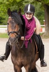 Mädchen sitzt auf ihrem Pferd