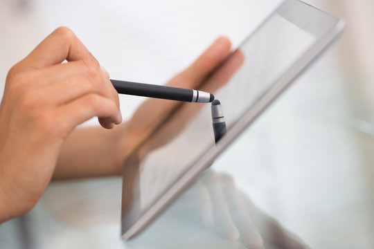 Close-up of woman working with stylus and digital tablet pc