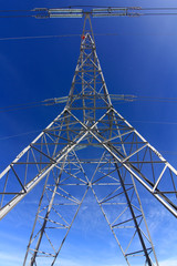 High voltage tower with blue sky behind