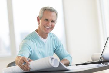 Happy Architect Holding Blueprint At Desk