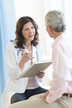 Doctor Discussing With Patient In Clinic