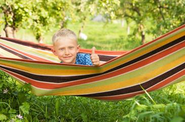 Little boy relax in hammock into the garden