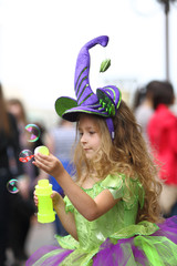 Little girl in fancy dress catching soap bubbles on holiday