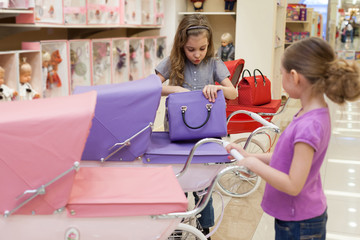 girls in toy store purchased a buggy and handbag