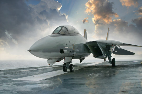 F-14 jet fighter on an aircraft carrier deck beneath dramatic cl