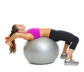 Fitness woman making exercise with dumbbells on fitness ball