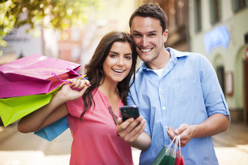 Happy couple using smart phone during the shopping .