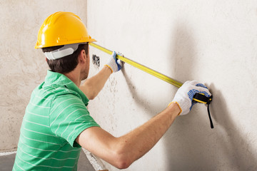 worker measuring plaster wall