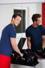 junger mann mit hanteln im fitnessstudio