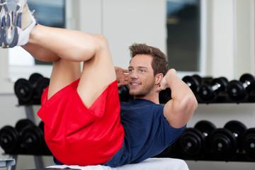 mann macht sit-ups im fitnessstudio