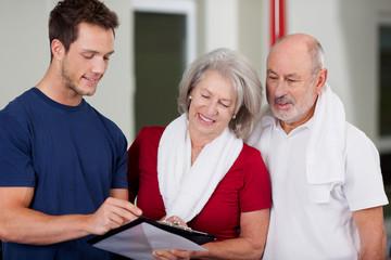 trainer berät älteres ehepaar im fitnessstudio