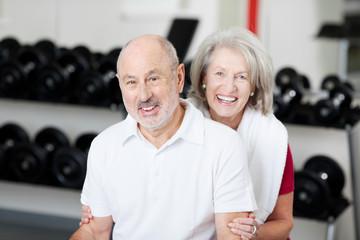lächelndes älteres paar im fitnessstudio