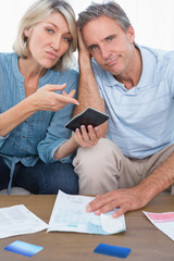 Anxious couple going over their debt looking at camera