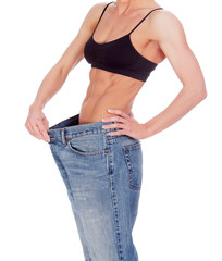 woman shows her weight loss by wearing an old jeans