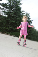 young happy girl riding roller blades outdoors