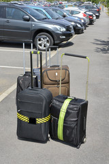 Suitcases just unloaded from vehicle in train station car park