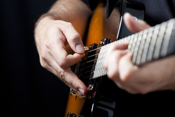 Wall Mural - Close up on  hands playing on electric guitar