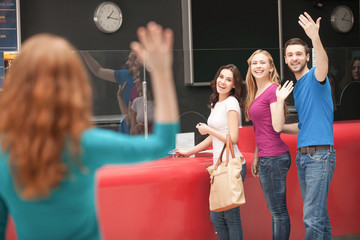 Friends meeting at the cinema. Cheerful young people greeting