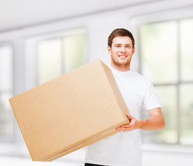 smiling man carrying carton box