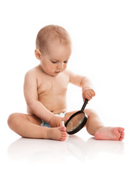 One-year old boy holding a magnifying glass over white