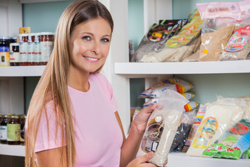 Woman Holding Food Packet In Grocery Store