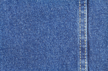Texture of blue jeans fabric with yellow stitching on right side