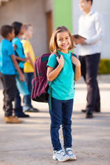 primary school student carrying backpack