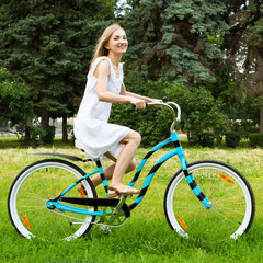 Young happy girl riding bicycle in a park