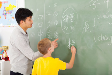 elementary school teacher helping young boy writing chinese