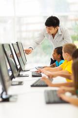 primary school teacher helping student in computer room