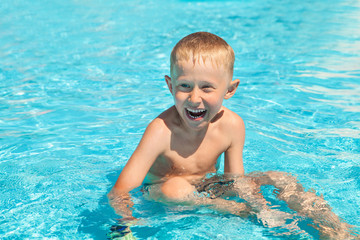 Emotional smiling little boy sitting into the pool