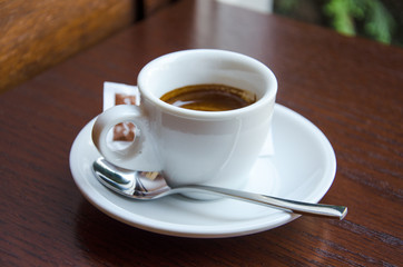 White espresso cup standing on the wooden table