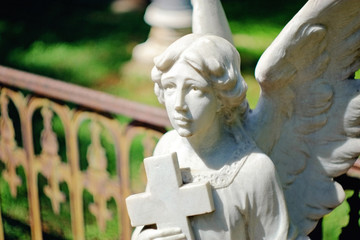 angel holding cross tombstone