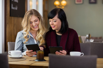 Female Friends With Digital Tablets At Coffeeshop