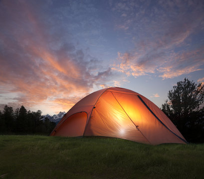 Tent with light inside at dusk near the Grand Teton mountains